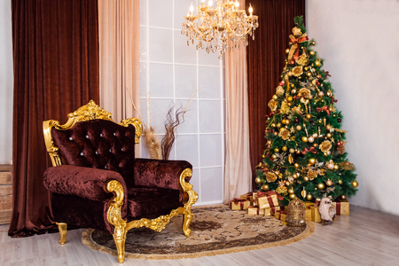 New year tree decorated with golden toys and balls, christmas interior background with luxury chair