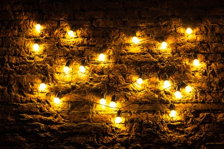 Brick wall with light bulbs glowing background