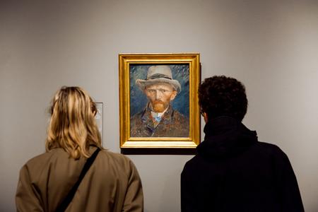 Bezoekers kijken naar zelfportretkunstwerken van de beroemde schilder Vincent van Gogh in het Rijsmuseum in de stad Amsterdam, Holland