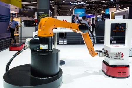 Kuka industrial robot on Huawei booth stand on Messe fair in Hannover, Germany