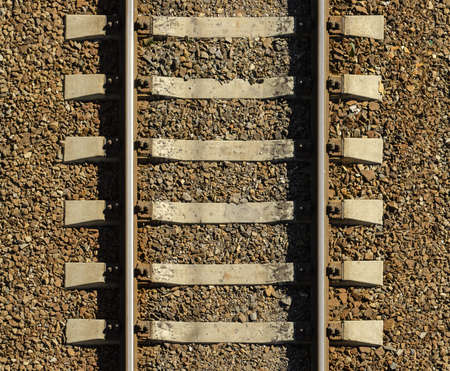 Seamless railroad Pattern, backdrop with space for text. Top view. Shiny iron rails and concrete sleepers, coupled with powerful bolts on stony ground, fortified rubble overgrown