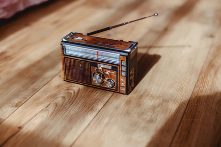 radio with wedding rings on the floor with sun shadows on the ground
