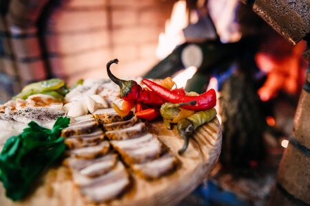 meat board with Ukrainian lard, pepper and vegetables on the background of fire
