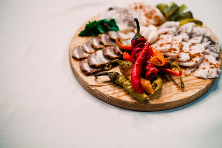 meat board with Ukrainian lard, pepper and vegetables on table