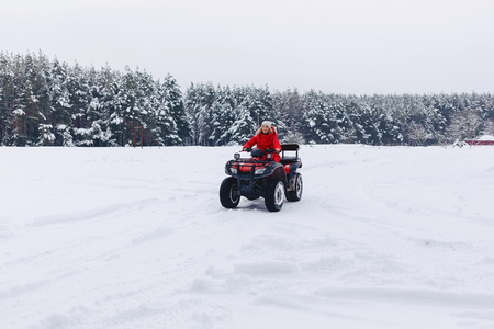 A pretty girl riding a quadrocycle in a picturesque snowy are at the countryside