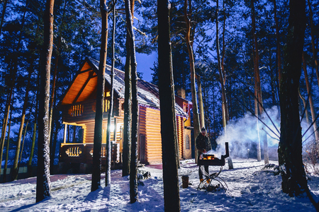 A man fries grilled meat against the background of the cottage in the evening and in the smoke in winter Stockfoto