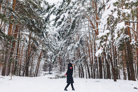 The girl walks in a snow-covered forest among the pines in red gloves poses and spins