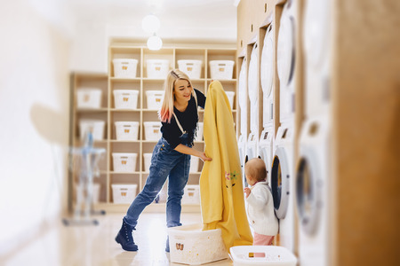 A woman with a child puts the sheets in the laundry with fun