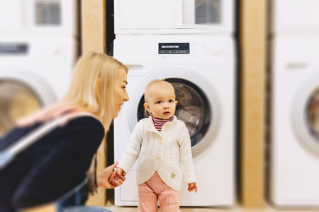 woman with baby near a washing machine have fun
