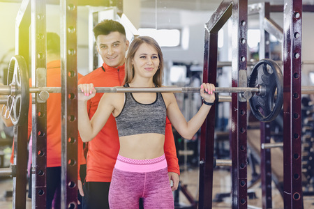 young girl doing squats with a barbell in the gym under the supervision of a trainer, healthy lifestyle