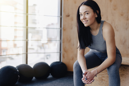 young girl in sportswear in a gym in a simple background, a theme of fitness, and sport, a healthy lifestyle