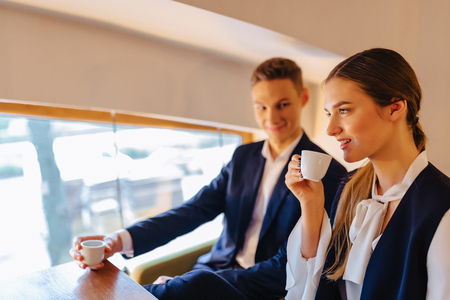 A stylish couple drinks morning coffee at the cafe with cozy interior, young businessmen and freelancers Stock Photo