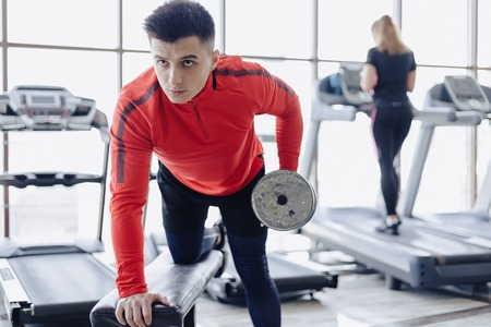 A man dumps triceps on the background of treadmills at the gym