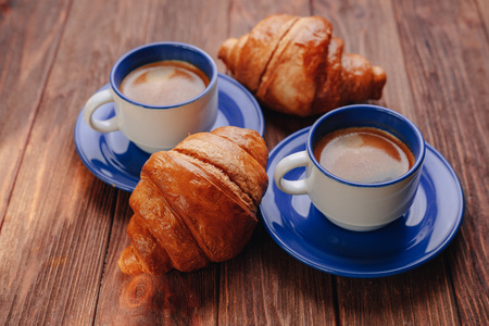 two cups of hot coffee and croissants on a wooden background, good light, morning atmosphere Banque d'images