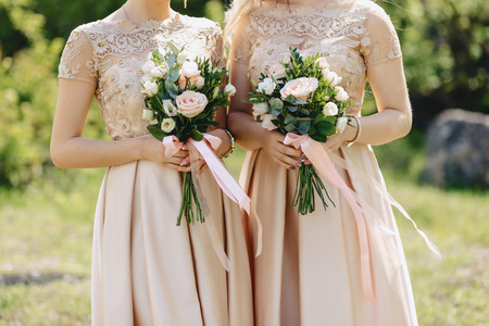 the bride holds a wedding bouquet in her hands, wedding day flowers