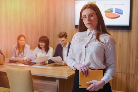 young attractive stylish office worker girl in glasses with a notebook in the hands on blurry background of working colleagues