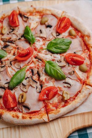 Neapolitanische Pizza auf Sahnesauce mit Champignons, Käse, Rucola, Basilikum, Tomaten mit Käse bestreut auf einem Holzbrett auf einer Tischdecke in einer Zelle mit Platz für den Text Standard-Bild