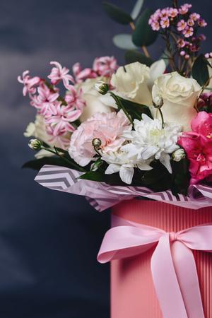 colored flower bouquet in basket on dark background