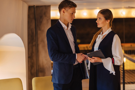 young businessmen guy and girl in a cozy interior have agreed, business and freelance in business style Imagens
