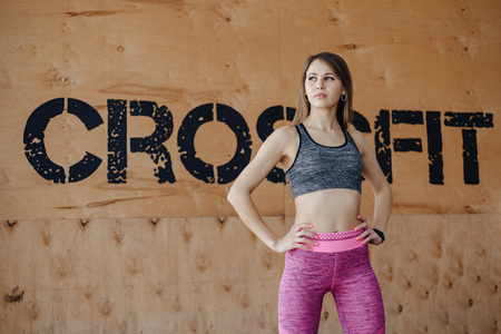 young girl in sportswear in a gym in a simple background, a theme of fitness, a crossfit and sport, a healthy lifestyle 版權商用圖片