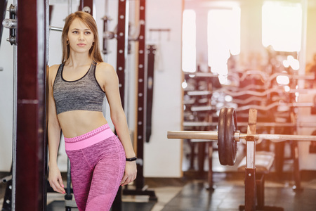 young fitness girl in the gym between the simulators, healthy lifestyle