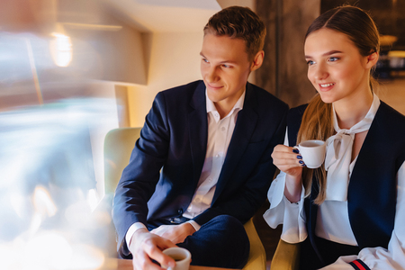 A stylish couple drinks morning coffee at the cafe with cozy interior, young businessmen and freelancers 스톡 콘텐츠