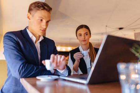 Una pareja elegante bebe café por la mañana en la cafetería con un interior acogedor y trabaja con una computadora portátil, jóvenes empresarios y autónomos