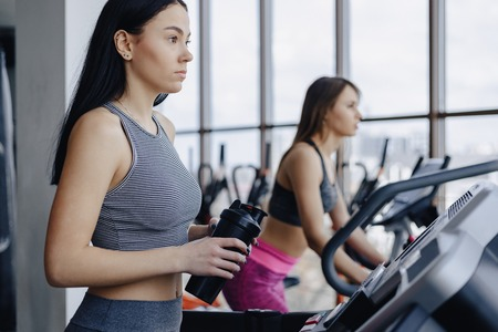 Girls in the gym are trained on treadmills and drink water, smiling and healthy