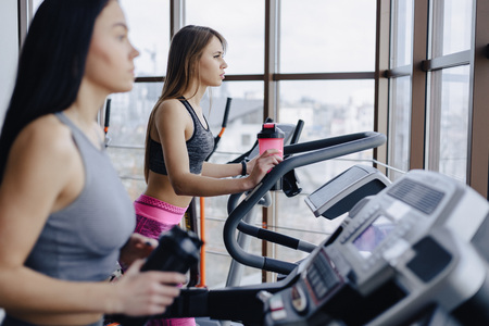 Girls in the gym are trained on treadmills and drink water, smiling and healthy Reklamní fotografie
