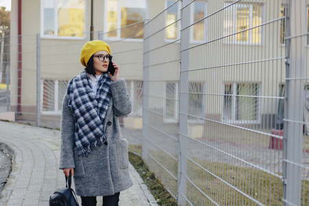 An attractive young girl wearing sunglasses in a coat and a beret walking down the street and talking on the phone and smiles Stock Photo