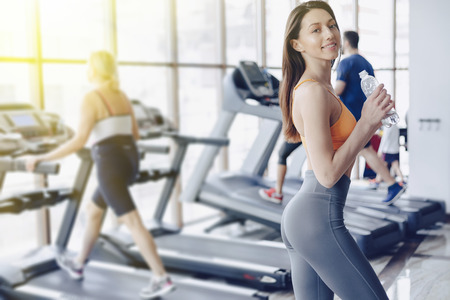 cozy young attractive girl in the gym drinking water on the background of treadmills