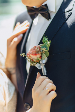 the groom holds elegant wedding bouquet in his hands
