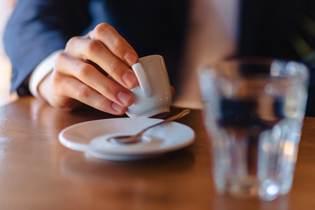 espresso coffee cup in stylish men's hand, morning coffee at cafe with copy space