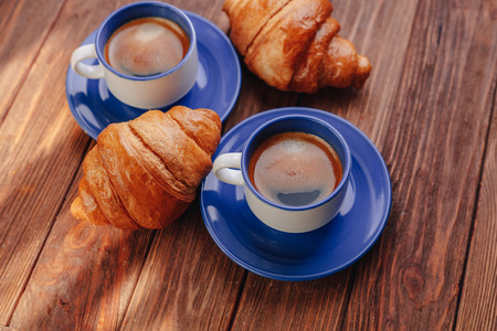 two cups of hot coffee and croissants on a wooden background, good light, morning atmosphere