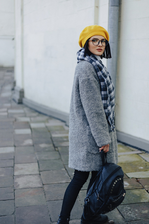 Attractive young girl in stylish glasses in coat and yellow Beret freestyle walking Stock fotó