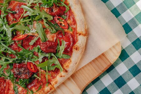 Neapolitan spicy pizza on a cream sauce with ham, cheese, arugula, basil, tomatoes, pepperoni pepper sprayed with cheese on a wooden board on a tablecloth in a cell with a place for text Stock Photo