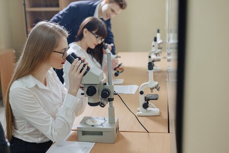 two girls and a boy work with microscopes at laboratory Фото со стока