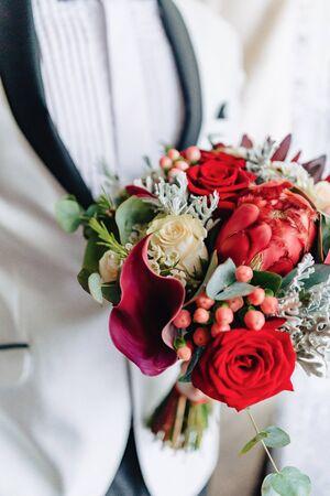 the groom holds elegant wedding bouquet in his hands