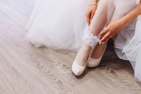 the bride wears delicate shoes on a wedding morning