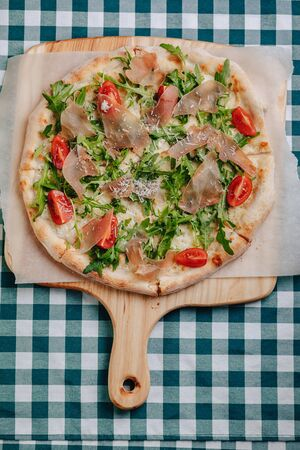 Neapolitan pizza on a cream sauce with salami, arugula, tomatoes sprinkled with cheese on a wooden board on a tablecloth in a cell with a place for text