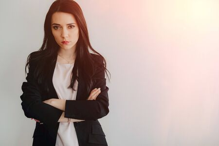 Young attractive emotional girl in business-style clothes on a plain white background in an office or audience alone Zdjęcie Seryjne