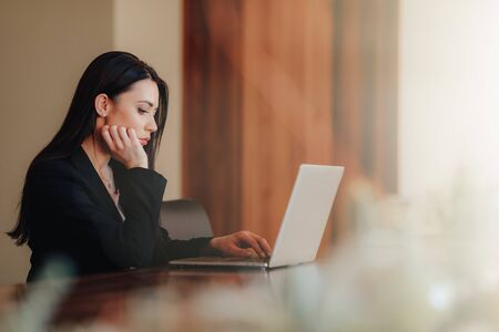 Young attractive emotional girl in business-style clothes sitting at a desk on a laptop and phone in the office or auditorium alone Foto de archivo - 132035288