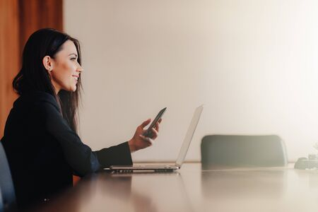 Young attractive emotional girl in business-style clothes sitting at a desk on a laptop and phone in the office or auditorium alone Foto de archivo - 132033576