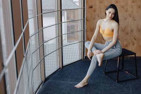 Young attractive fitness girl sitting on chair near the window on the background of a wooden wall, resting on yoga classes at gym Imagens - 132033352