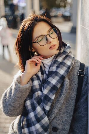 Attractive young girl wearing glasses in a coat on a urban background walking on a sunny day Imagens - 133458413