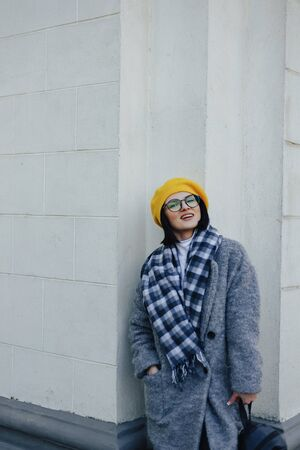 Attractive young girl in stylish glasses in coat and yellow Beret on a simple light background