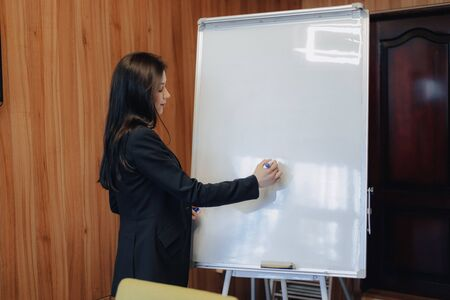 young emotional attractive girl in business-style clothes working with flipchart in a modern office or audience alone Imagens - 133458429
