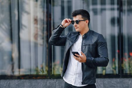 young stylish guy in glasses in black leather jacket with phone on simple glass background Imagens - 133458432