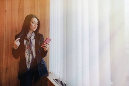 young emotional attractive girl in business-style clothes at a window with a telephone in a modern office or auditorium alone Imagens - 133458540