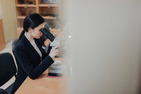 Young emotional attractive girl sitting at the table and working with a microscope in a modern office or audience alone Imagens - 133458664